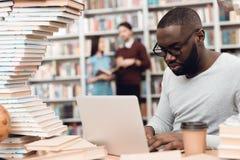 Etnische Afrikaanse Amerikaanse die kerel door boeken in bibliotheek wordt omringd De student gebruikt laptop en drinkt koffie royalty-vrije stock fotografie