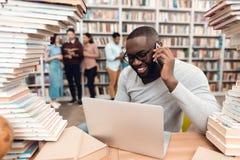 Etnische Afrikaanse Amerikaanse die kerel door boeken in bibliotheek wordt omringd De student gebruikt laptop en spreekt op telef royalty-vrije stock fotografie