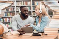 Etnische Afrikaanse Amerikaanse kerel en wit die meisje door boeken in bibliotheek wordt omringd De studenten gebruiken tablet royalty-vrije stock foto's