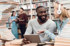 Etnische Afrikaanse Amerikaanse kerel en wit die meisje door boeken in bibliotheek wordt omringd De studenten gebruiken tablet stock afbeelding