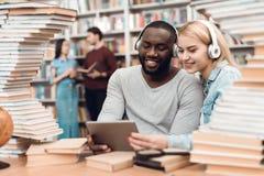 Etnische Afrikaanse Amerikaanse kerel en wit die meisje door boeken in bibliotheek wordt omringd De studenten gebruiken tablet royalty-vrije stock foto