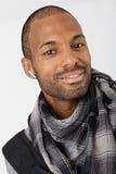Etnische kerel die met earbuds glimlacht Stock Foto's