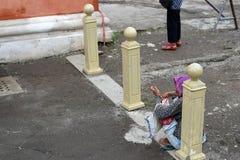 Etnische oude vrouwenzitting op bestrating die voor aalmoes bij oude kerkyard bedelen stock foto's