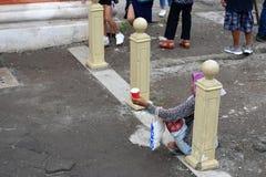 Etnische oude vrouwenzitting op bestrating die voor aalmoes bij oude kerkyard bedelen stock afbeelding
