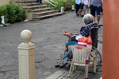 Etnische oude vrouwenzitting op de doos die van de Kerstmisgift van de rolstoelholding voor aalmoes bedelen royalty-vrije stock foto's