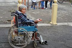 Etnische oude vrouwenzitting op de doos die van de Kerstmisgift van de rolstoelholding voor aalmoes bij oude kerkyard bedelen Slu royalty-vrije stock foto's