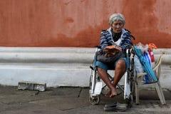 Etnische oude vrouwenzitting op de doos die van de Kerstmisgift van de rolstoelholding voor aalmoes bij oude kerkyard bedelen Slu stock foto