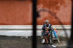 Etnische oude vrouwenzitting op de doos die van de Kerstmisgift van de rolstoelholding voor aalmoes bij oude kerkyard bedelen Slu stock foto's