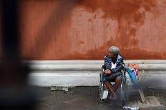 Etnische oude vrouwenzitting op de doos die van de Kerstmisgift van de rolstoelholding voor aalmoes bij oude kerkyard bedelen Slu royalty-vrije stock fotografie