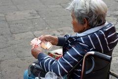 Etnische oude vrouwenzitting op geld van de rolstoel het tellende aalmoes bij oude kerkyard Sluit omhoog stock afbeelding