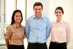Etnische professionele medewerkers die bij u glimlachen royalty-vrije stock afbeeldingen
