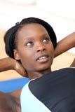 Etnische vrouw in gymnastiekuitrusting die zitten-UPS doet Royalty-vrije Stock Afbeelding