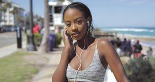 Etnische vrouw in oortelefoons en sportkleding bij kust stock video
