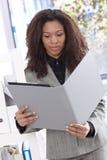 Etnisk affärskvinna som ser mappen Arkivbilder