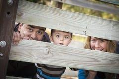Etnisk familj för blandad Race som ser till och med staket Royaltyfri Foto