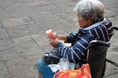 Etnisk gammal kvinna som sitter på rullstolen som räknar allmosapengar på den gamla kyrkliga gården close upp royaltyfria bilder