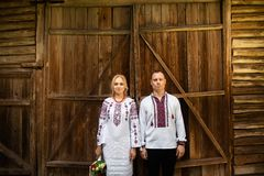 Etniskt br?llop i nationella dr?kter Ukrainskt förbindelsebrud- och brudgumanseende på bakgrunden av en trävägg royaltyfri foto