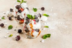Eton mess with blackberries. Traditional English dessert. Eton mess - whipped cream, meringue, fresh blackberries, sauce and caramel. In serving glasses on a Royalty Free Stock Photography