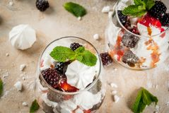 Eton mess with blackberries. Traditional English dessert. Eton mess - whipped cream, meringue, fresh blackberries, sauce and caramel. In serving glasses on a Stock Photo