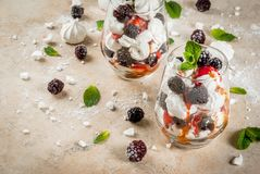 Eton mess with blackberries. Traditional English dessert. Eton mess - whipped cream, meringue, fresh blackberries, sauce and caramel. In serving glasses on a Royalty Free Stock Image