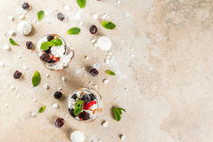 Eton mess with blackberries. Traditional English dessert. Eton mess - whipped cream, meringue, fresh blackberries, sauce and caramel. In serving glasses on a Royalty Free Stock Photos