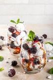 Eton mess with blackberries. Traditional English dessert. Eton mess - whipped cream, meringue, fresh blackberries, sauce and caramel. In serving glasses on a Stock Photos
