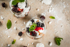 Eton mess with blackberries. Traditional English dessert. Eton mess - whipped cream, meringue, fresh blackberries, sauce and caramel. In serving glasses on a Stock Images