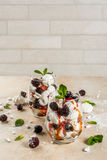 Eton mess with blackberries. Traditional English dessert. Eton mess - whipped cream, meringue, fresh blackberries, sauce and caramel. In serving glasses on a Stock Photography