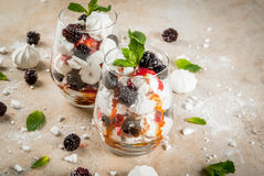 Eton mess with blackberries. Traditional English dessert. Eton mess - whipped cream, meringue, fresh blackberries, sauce and caramel. In serving glasses on a Stock Image