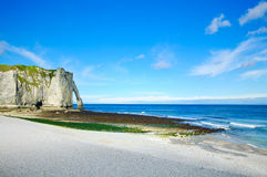 Etretat Aval cliff landmark. Normandy, France. Etretat Aval cliff landmark and its beach and a blue sky. Normandy, France, Europe Stock Photos