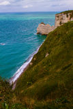 Etretat cliffs, France. Etretat  chalk cliffs, including three natural arches and a pointed formation called L`Aiguille or the Needle.  Seine-Maritime department Royalty Free Stock Image