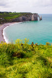 Etretat cliffs, France. Etretat  chalk cliffs, including three natural arches and a pointed formation called L`Aiguille or the Needle.  Seine-Maritime department Stock Image