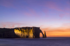 Etretat cliffs, France. Etretat steep arch shaped cliff at sunset,  Normandy, France Stock Images