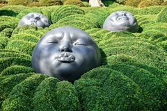 ETRETAT, FRANCE - SEPTEMBER 02, 2018: Giant rubber heads sleeping on green pillows. Boxwood garden in the famous garden of Etretat stock photo