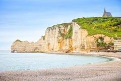 Etretat klippa, kyrklig gränsmärke och strand på morgon Normandie F Arkivbild