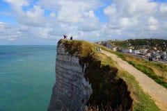 Etretat Los turistas audazes miran el mar del borde de un acantilado fotos de archivo