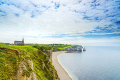 Etretat, ocean, church and Aval cliff landmark. Normandy, France. Royalty Free Stock Photos