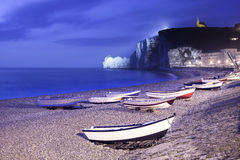 Etretat village, bay beach and boats on foggy night. Normandy, France. Stock Images