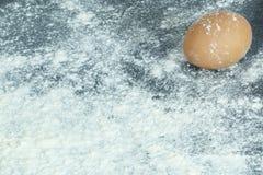Ett ägg på en yttersida som täckas i mjöl Royaltyfri Fotografi