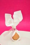Ett ägg som binds i en servett, som ser som kanin, gå i ax Arkivfoto