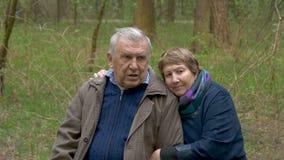 Ett äldre härligt parsammanträde i ett trä, på ett sågat trä De talar, kramar ömt, den förälskade blicken på de stock video