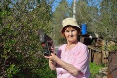 Ett äldre kvinnaträdgårdsmästareanseende med en elektrisk beskärare i t royaltyfri fotografi