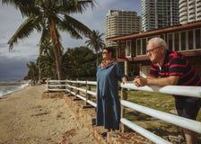 Ett äldre par nära hans hem på kusten som håller ögonen på den annalkande stormen tropisk semesterort Arkivfoton