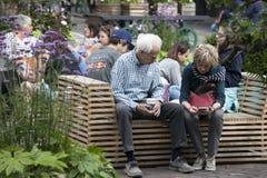 Ett äldre par sitter på en bänk som ser in i telefonen En liten trädgård i mitten av den Covent trädgården Arkivfoto