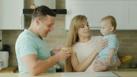 Ett älska par av föräldrar matar deras behandla som ett barn från skeden Lek med honom, roar honom Lycklig familj, sunt äta lager videofilmer