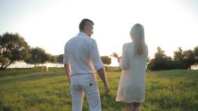 Ett älska par går i bakgrunden av solen arkivfilmer