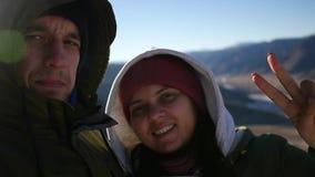 Ett älska par gör selfie överst av berget, med en gest av segern på fingrarna Ultrarapid 1920x1080 stock video