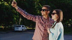 Ett älska par gör selfie I strålarna av solen utomhus lager videofilmer