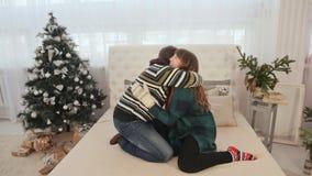 Ett älska par har gyckel och dansar på sängen julhelgdagsaftongåvor semestrar många prydnadar Varm atmosfär för ` s för nytt år stock video