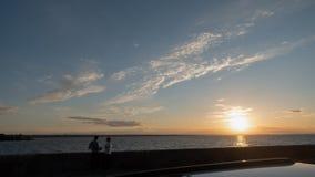 Ett älska par i kontur på kusthavet Arkivfoton